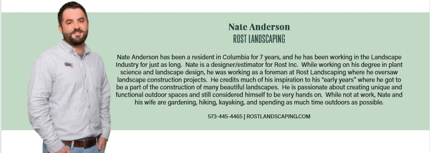 Nate Anderson of Rost Landscaping posing in a dark grey long sleeve shirt in front of a light green background.