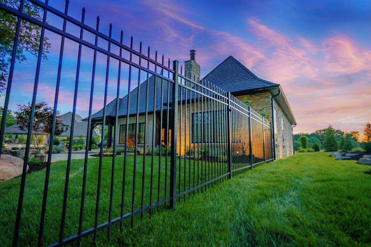 Ornamental fencing in backyard with freshly cut green grass.